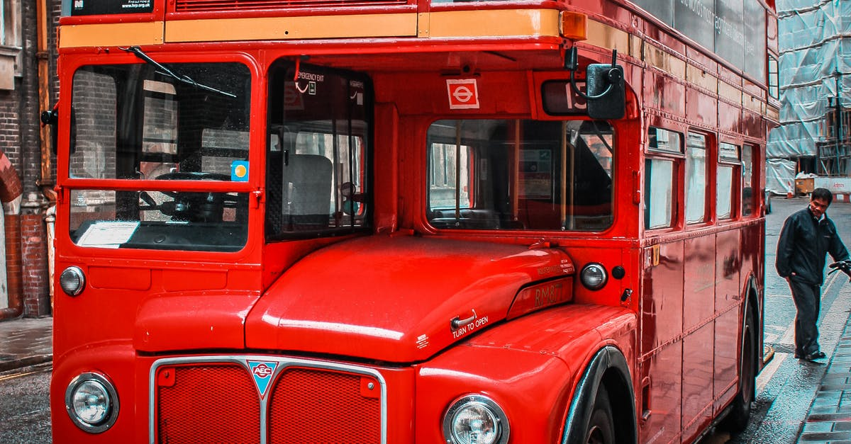 A double decker bus parked in front of a car